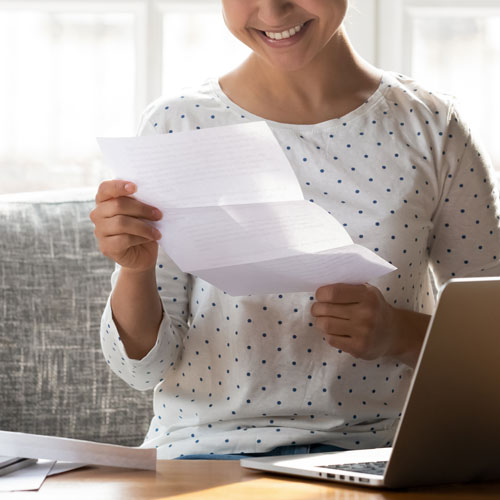 A young woman holding a letter smiles with joy.