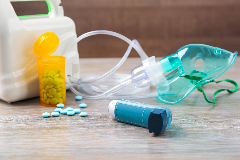 A photo of an asthma inhaler, nebulizer, and bottled medication.
