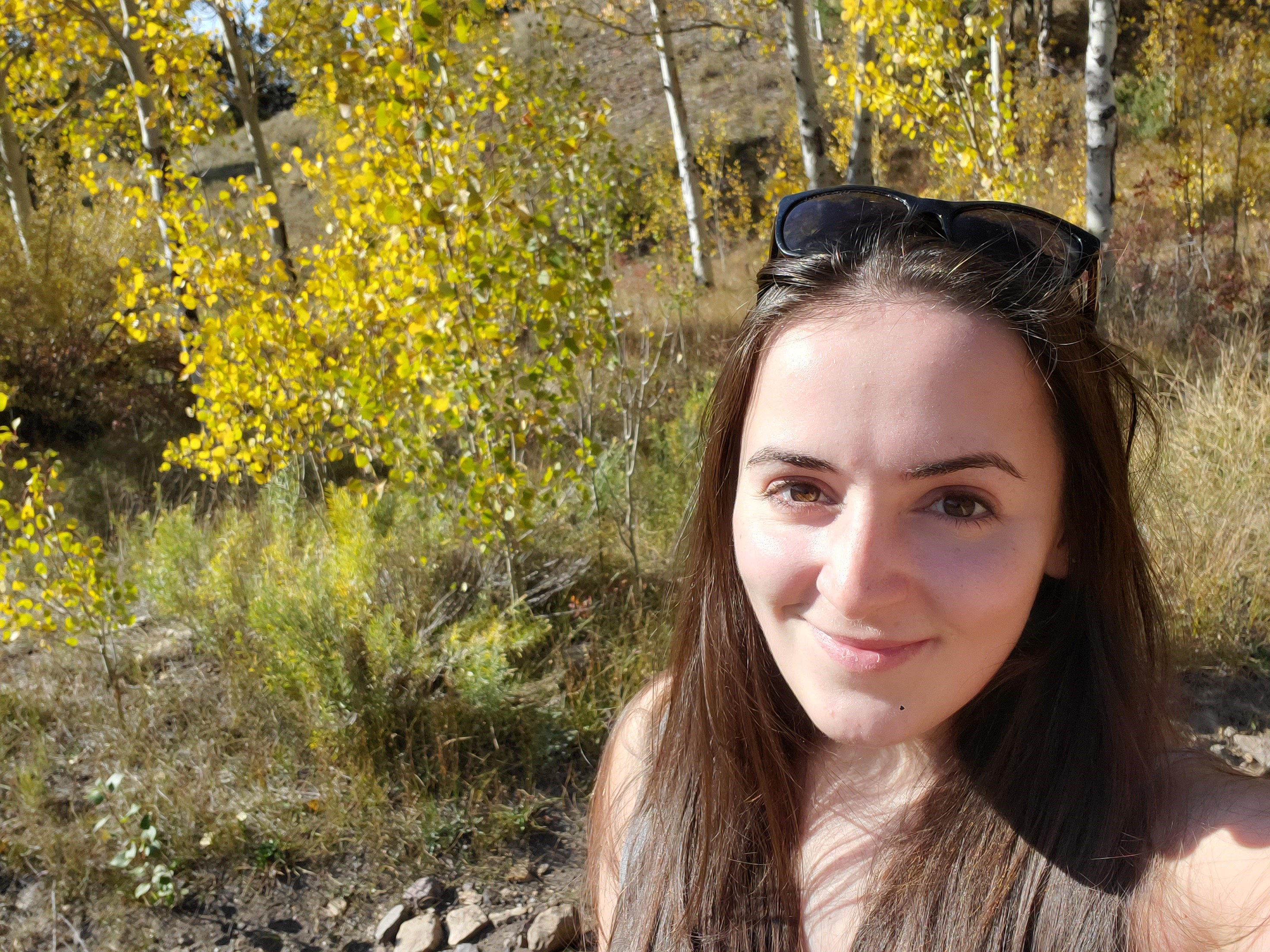 Anna Leggett takes a selfie of herself while hiking in the woods.