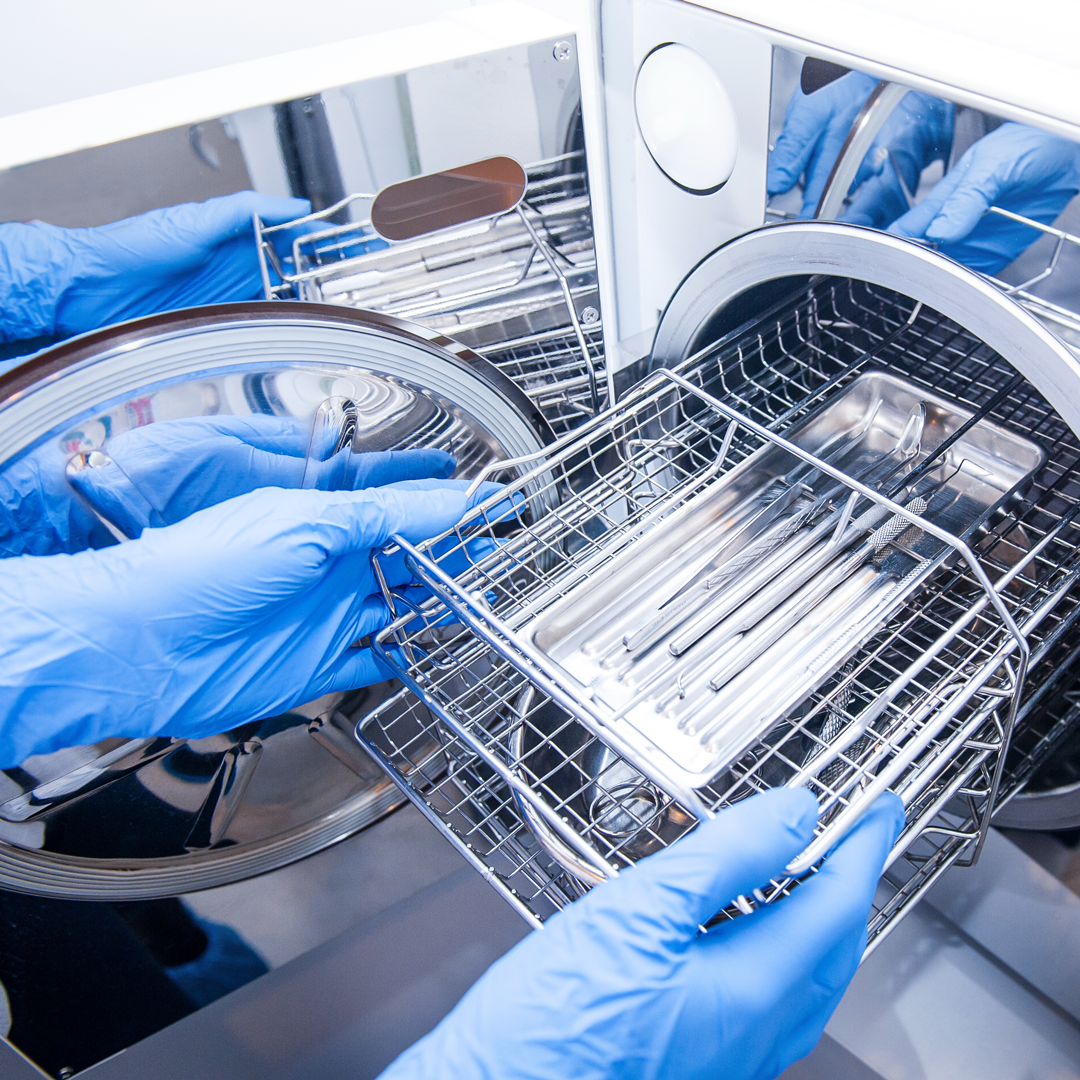A technition inserts dental instruments into an autoclave for steam sterilization.
