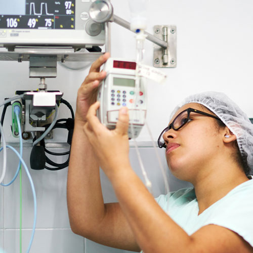 A biomedical engineering technician sets up a medical device in a hospital room.