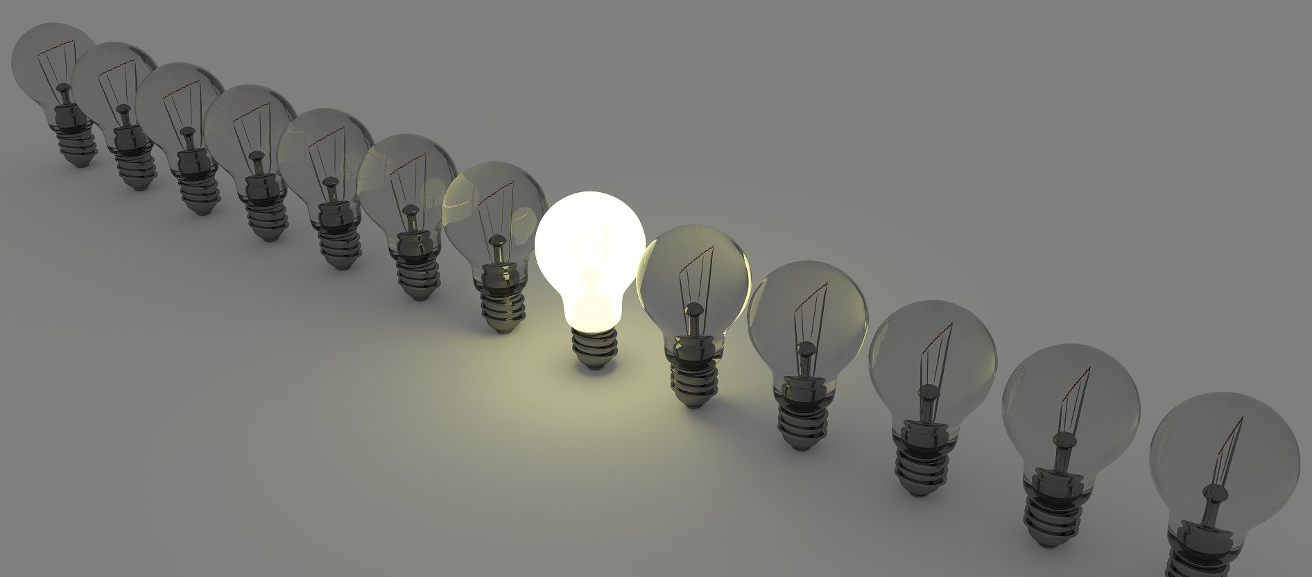 Light bulbs standing in a row. Only one light bulb is brightly illuminated.
