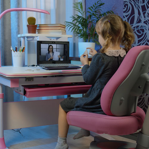 A little girl watches a woman present through video chat.