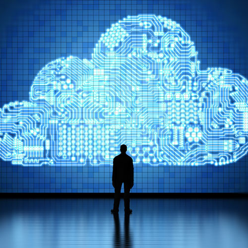 Man stands dwarfed by a technological cloud