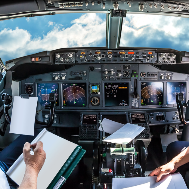 Pilots take notes in the cockpit of a plane.