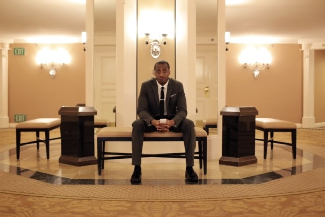 Darren Robertson dressed in a suit and sitting in a hotel lobby.