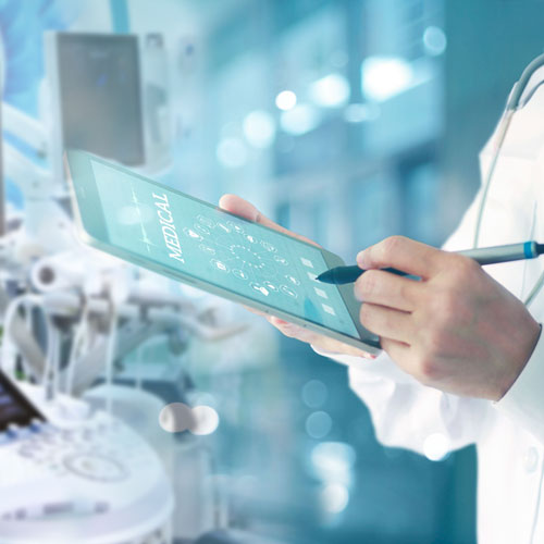 A doctor works on a tablet with medical devices in the background.