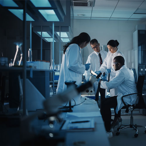 Researchers in lab coats gather around a work station.