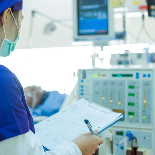 A technician with a clipboard inspects a medical device next to a hospital patient