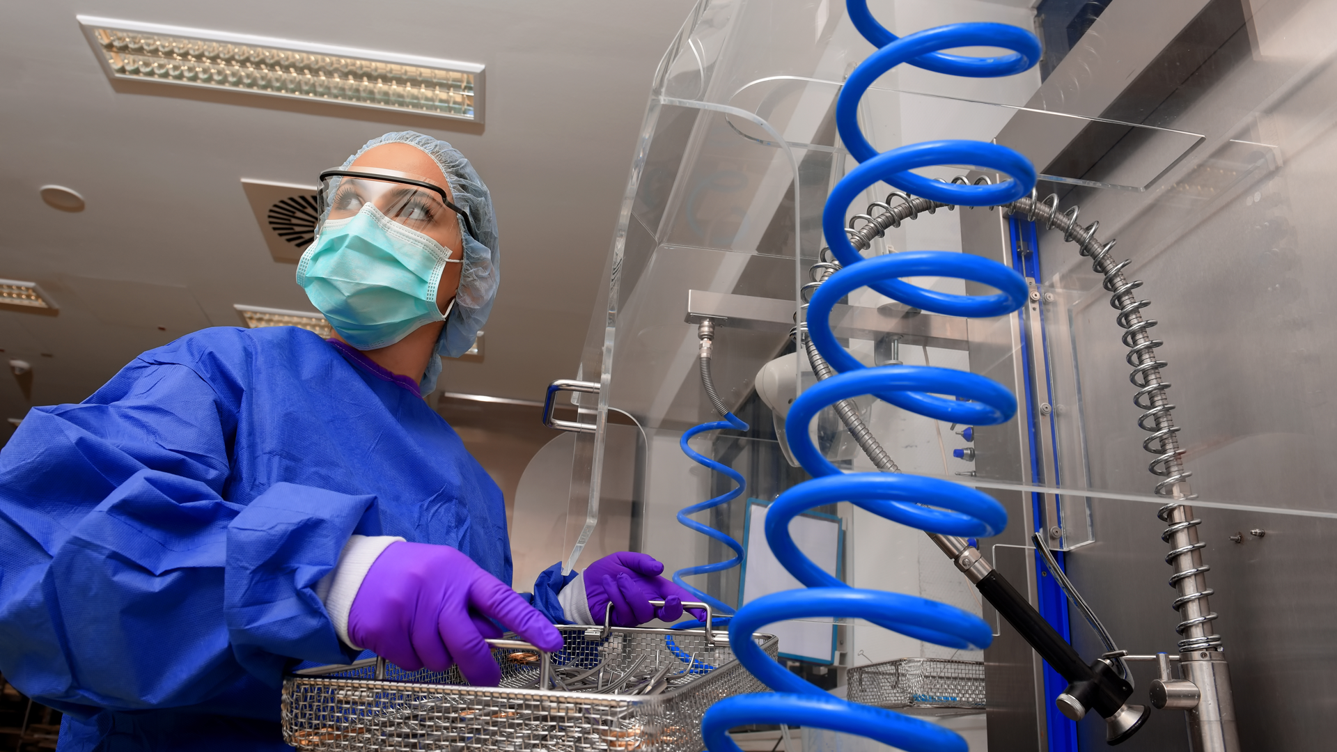A hospital sterilization professional in full PPE prepares medical instruments for cleaning.