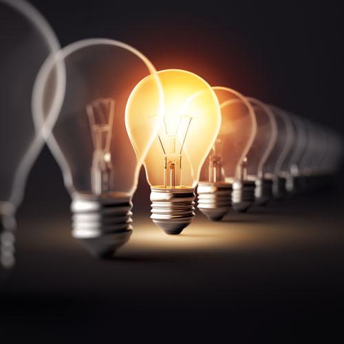 A row of unlit lightbulbs and a single lit one.