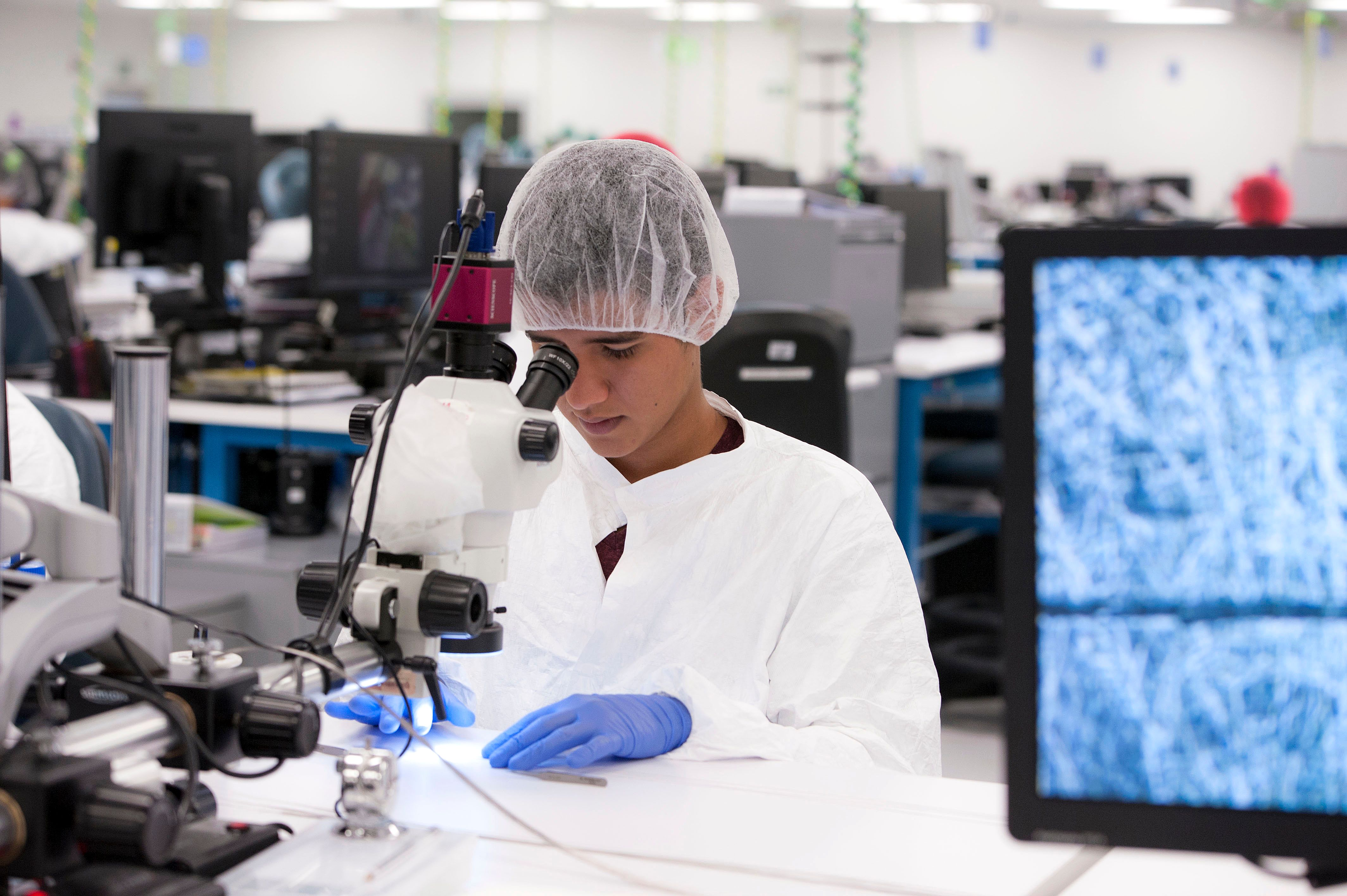 A Costa-Rican employee of Microvention inspecting a device for quality assurance.