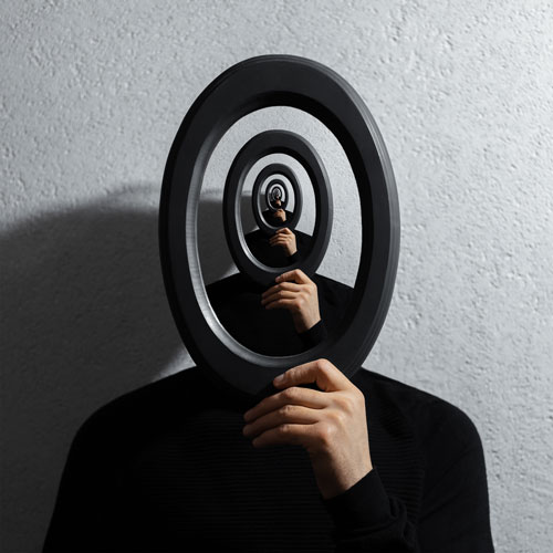 A man holds a mirror in front of his face. The image is reflected into the mirror repeatedly, creating an optical illusion.
