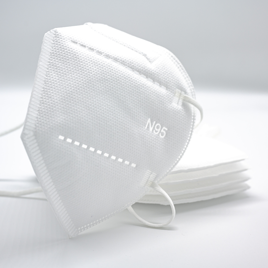 A white N95 mask lies on a table.