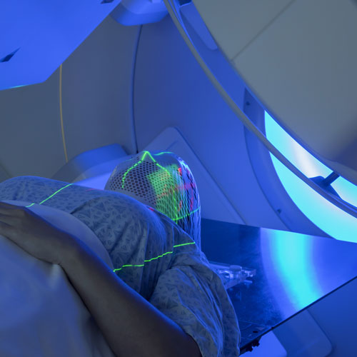A woman receives radiation therapy. Her face is covered.