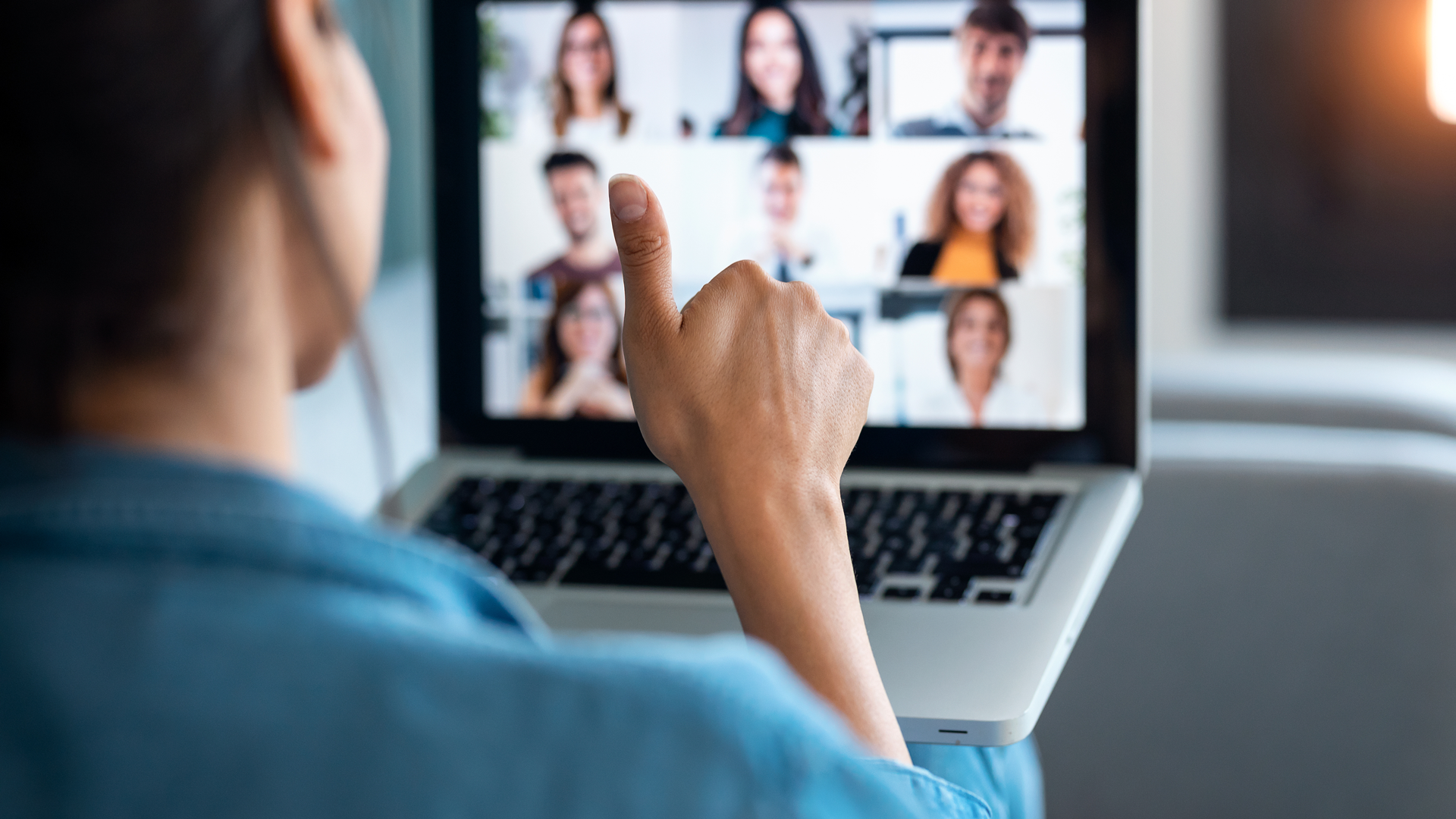 A remote meeting participant gives a thumbs up while facing her laptop. Video call participants can been seen on the laptop's screen.