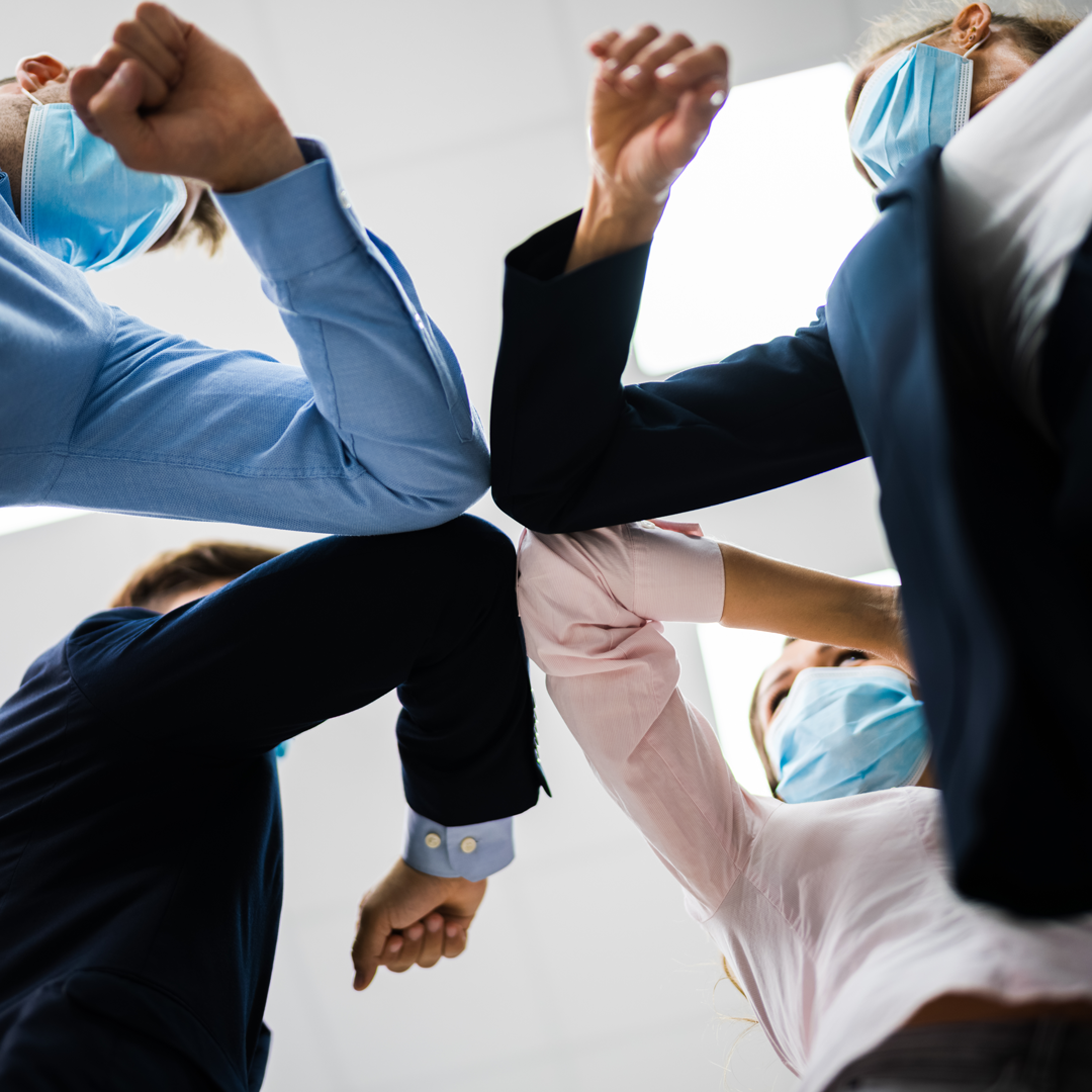 Four people in business casual clothes and masks elbow bump.