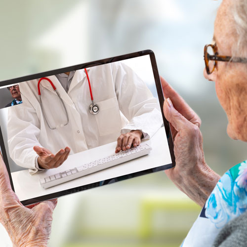 A patient uses a digital tablet to speak with her doctor.
