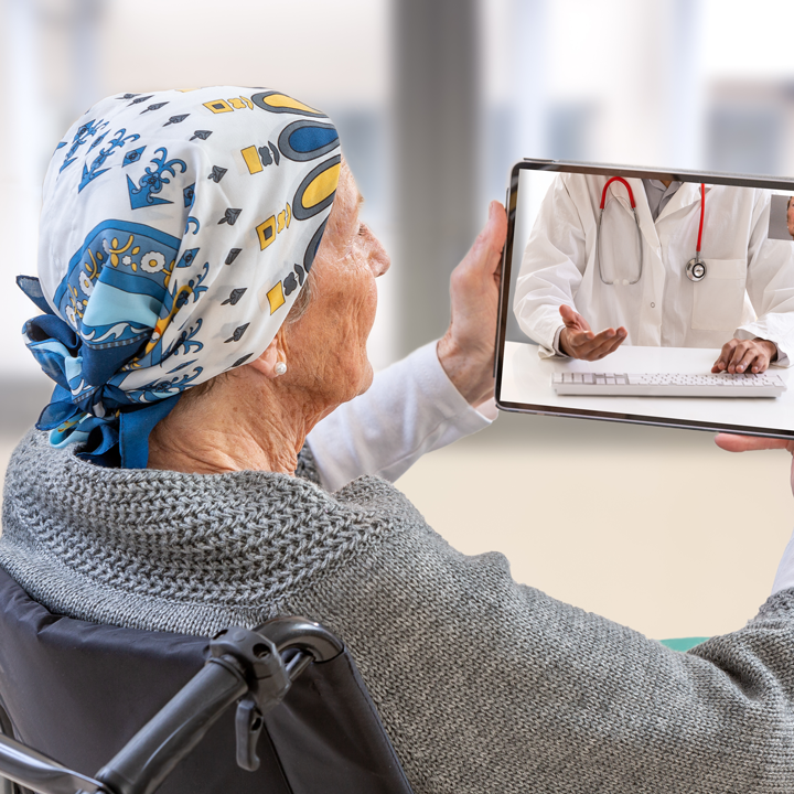 A senior woman video calls with her doctor using a tablet.